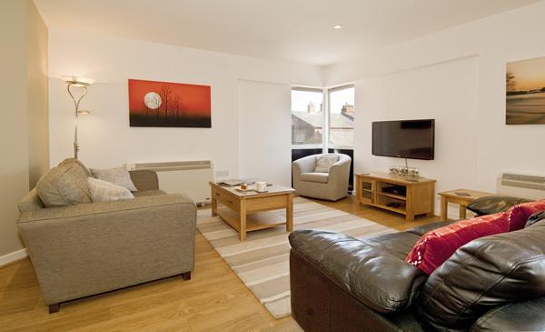 Lounge with comfortable sofas, balcony and 40' Smart TV with wireless keyboard.