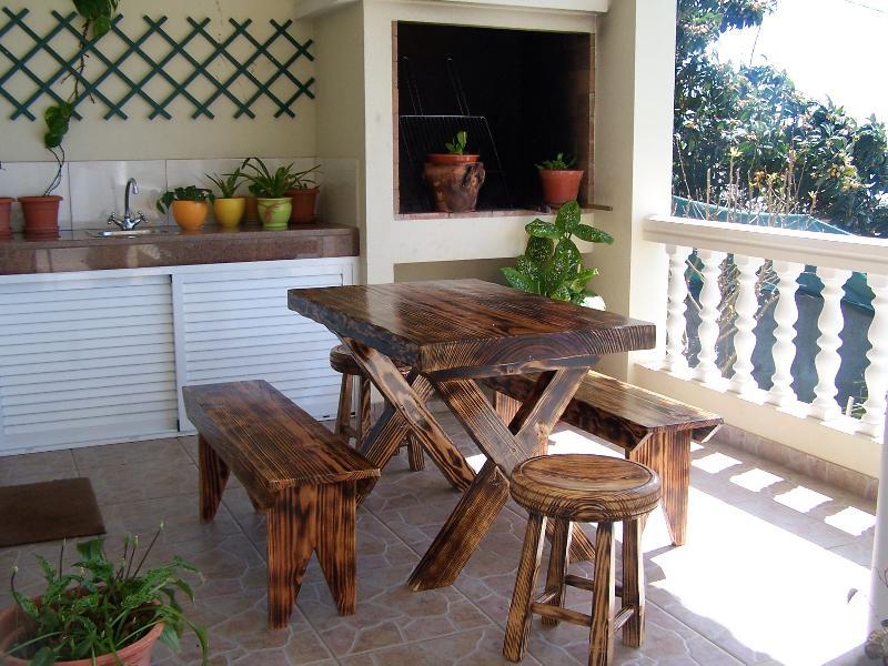 zona de la terraza fuera de la cocina con barbacoa, zona de lavabo exterior y mesa de madera tradicional y bancos