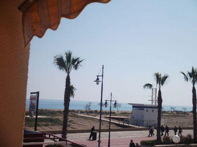 Vista  desde la terraza al paseo maritimo y playa norte de peñiscola.Mesa y dos sillas, toldo...