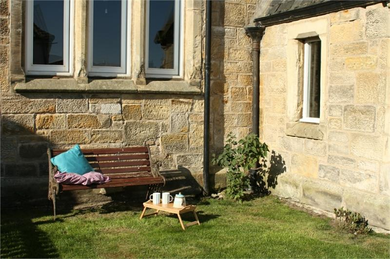 Cuidadosamente colocado banco no jardim da frente para pegar o sol da manhã com sua xícara de chá e um bom livro.