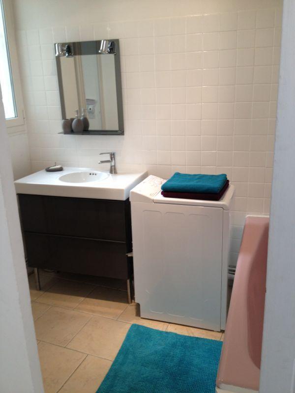 Salle de bain avec machine à laver neuve, lavabo et meubles neufs. WC attenants avec fenetres