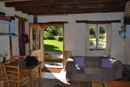 Sitting room of Le Gite au Chez looking out onto its garden.