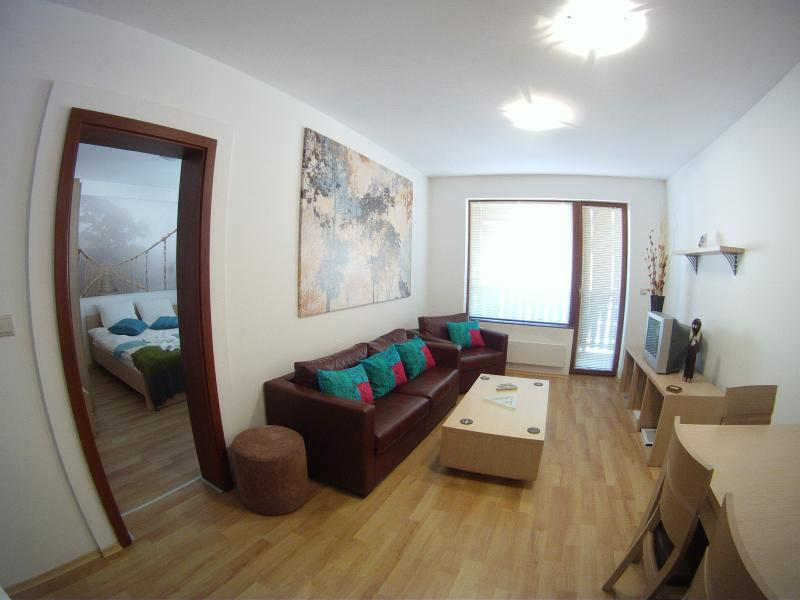 Cosy lounge area with access to main bedroom. Comfy chairs to relax, with TV/DVD.  Access to balcony