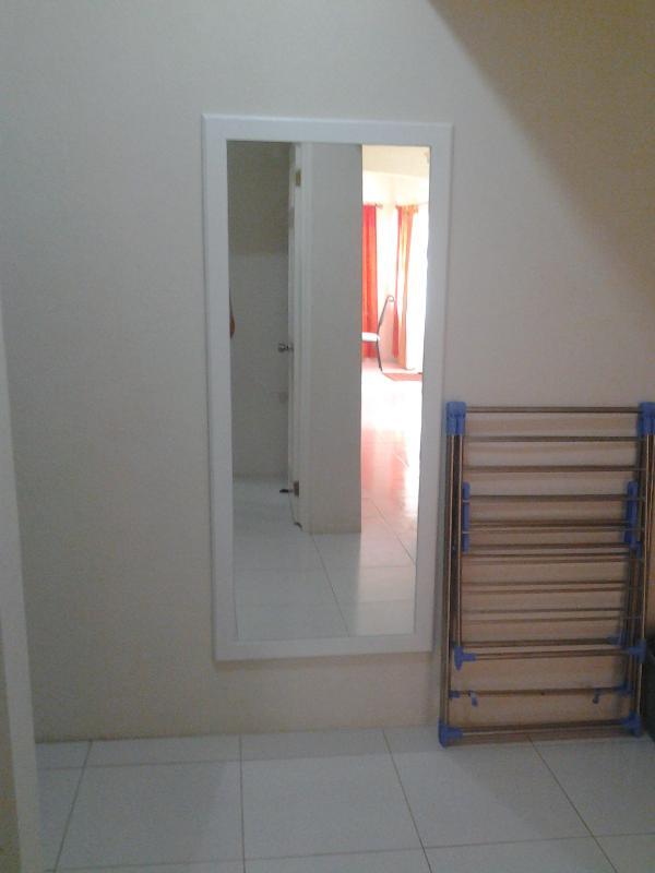 Miroir pleine hauteur et étendoir dans le hall menant à la chambre et à la salle de bain