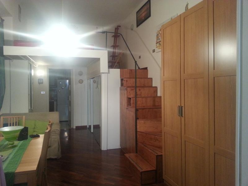 la camera da pranzo con divanetto  e scala verso il soppalco