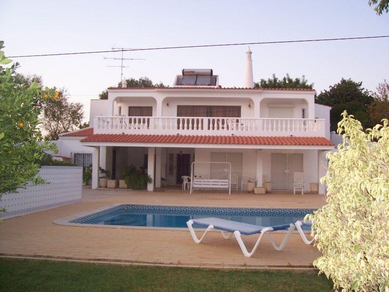 View of the property with swimming pool and sun loungers