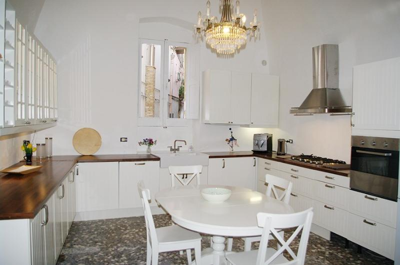 Bright very well fitted kitchen, cathedral ceiling, dining table under crystal chandelier.