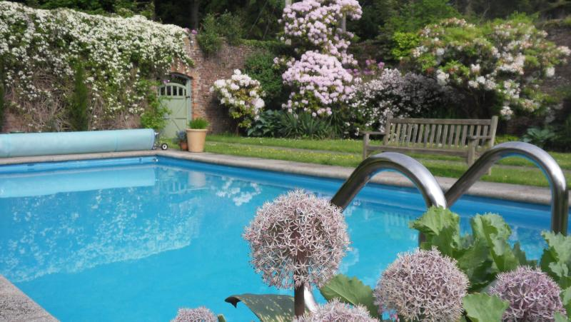Coastal holiday cottage with outdoor heated pool by Rigg Bay within large beautiful walled garden.