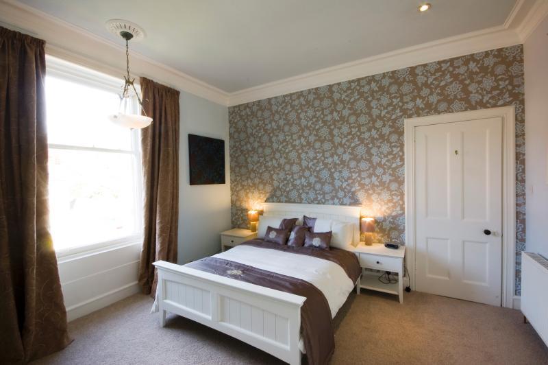 2 dormitorios con cama de matrimonio con vistas a la parte delantera de la propiedad