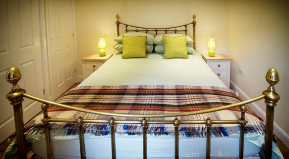 Brass Bed with blackout blinds, mobile phone charging station, dressing gowns, slippers.