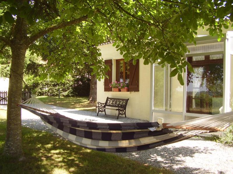 The double hammock hangs under the walnut tree