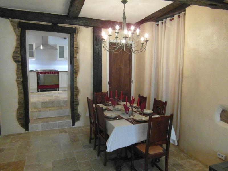 A dining table crowned by a chandelier seating six to twelve happy diners