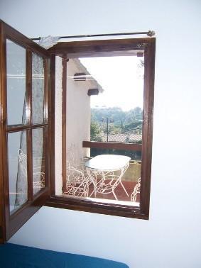 Ventana de la habitación con dos camas individuales de la planta piso con vistas a la terraza
