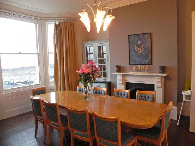 the dining room which comfortably seats 12 guests, with bay window overlooking the beach