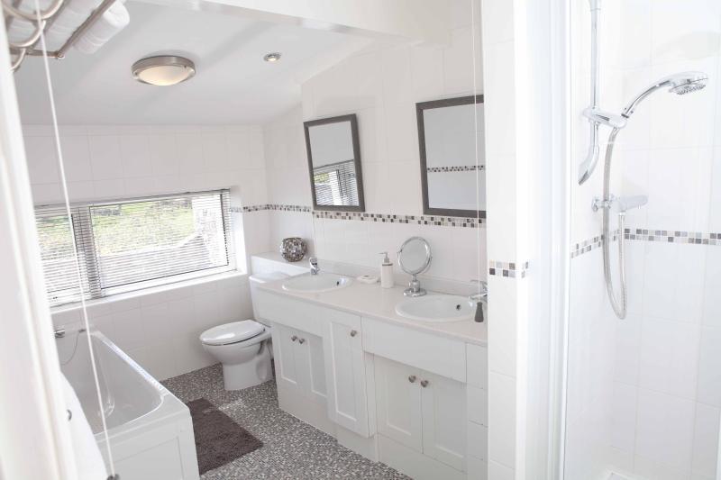 Modern bathroom with twin handbasins, bath with shower & seperate walk in shower.