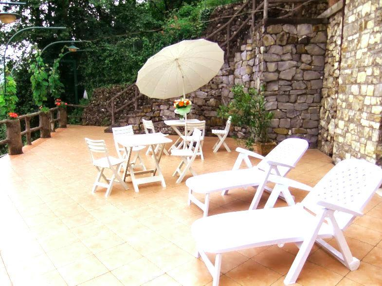 Sunny day on the terrace with sun ombrella, chaises longue, table and chairs