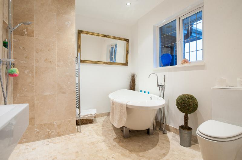 New Travertine and porcelain bathroom, luxurious deep bath.