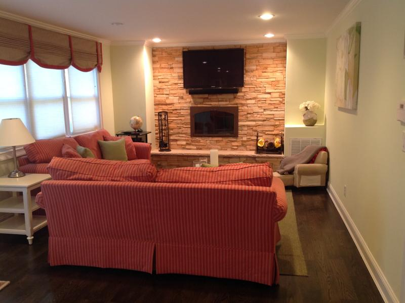 Cozy family room to relax and wind down with fire place and smart tv