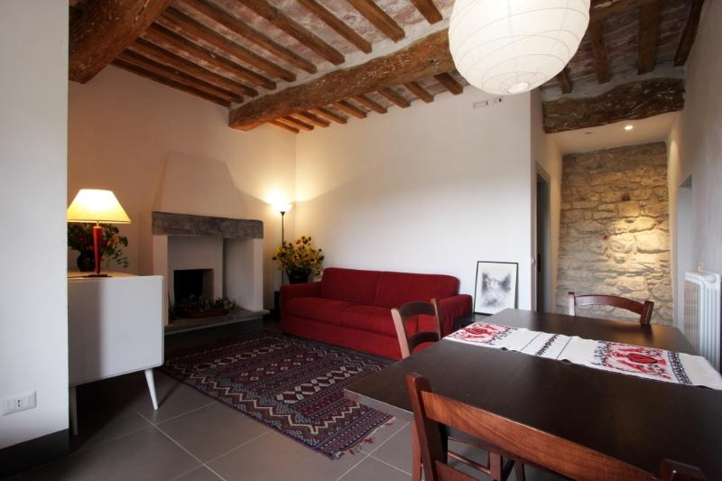 the living room with the old fireplace and the tower's wall