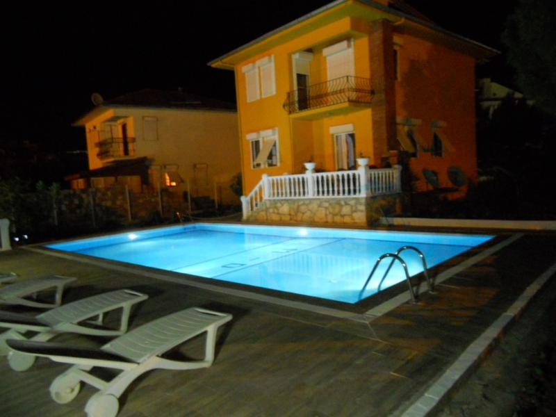 A nice view of the swimming pool and the property during the night
