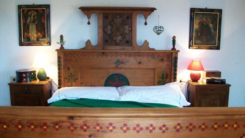 Una pintada a mano y cama tallada en el dormitorio de