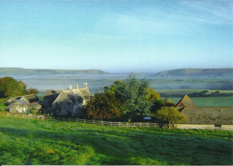 Corfe Castle in the distance, the house on the left and the holiday barns on the right