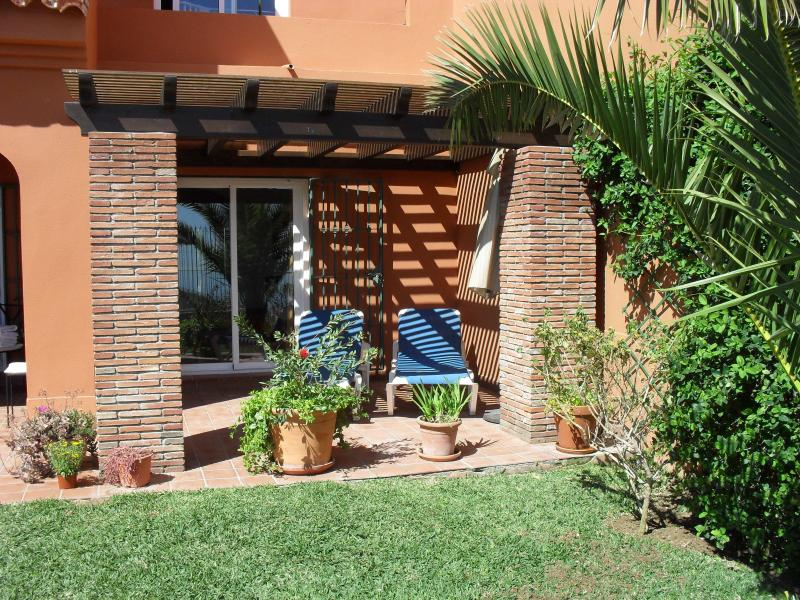 Relax under the pergola on sun loungers