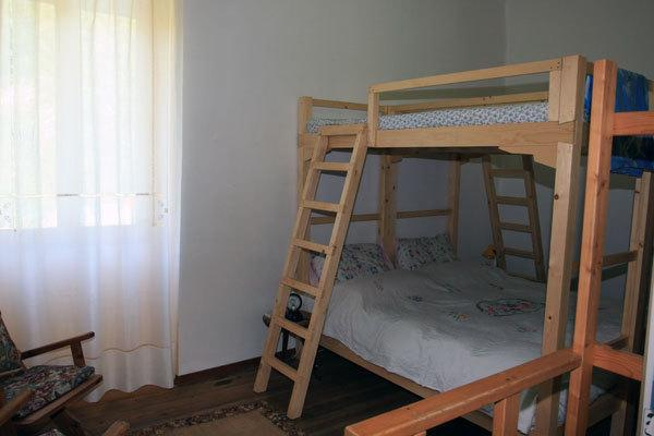 A spiral staircase leads to the large bedroom with 4 beds
