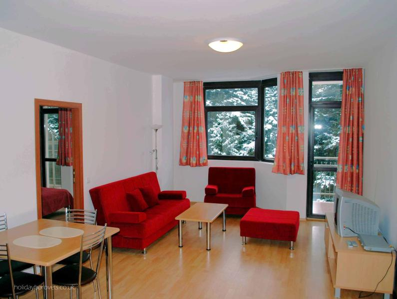 Spacious lounge with sofa bed (sleeps 2). Balcony looks over pine trees