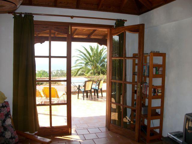 Sala de estar com TV, livros e vista mar