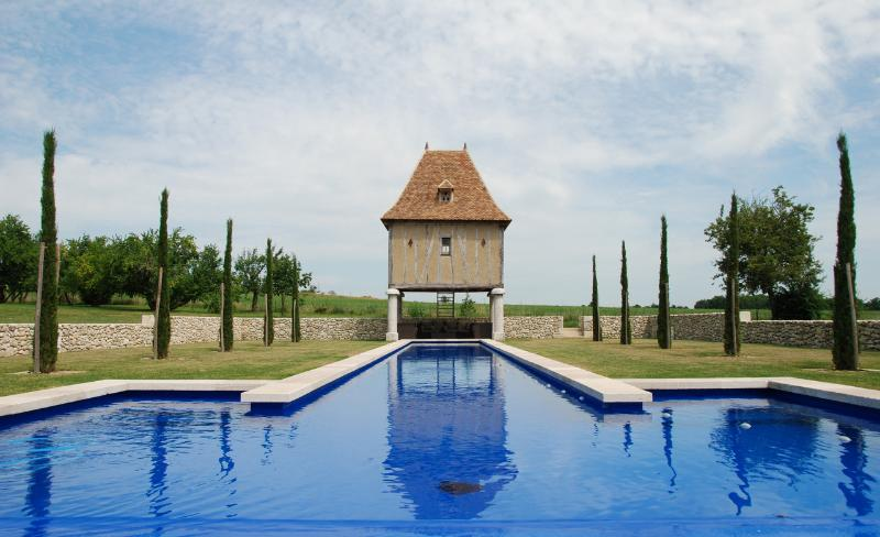 The 29 metre long swimming pool viewed from the infinity edge to pigeonnier