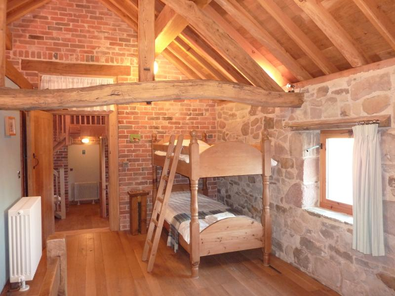 Master bedroom with bunk beds - beautiful exposed original features of stone & brick wall, oak b