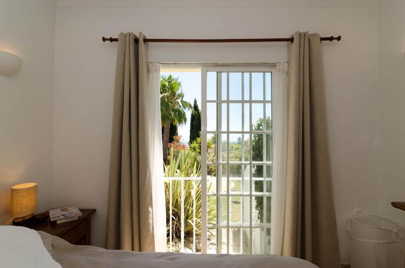Over hoofdslaapkamer met het oog op venster met uitzicht op zwembad met uitzicht op zee
