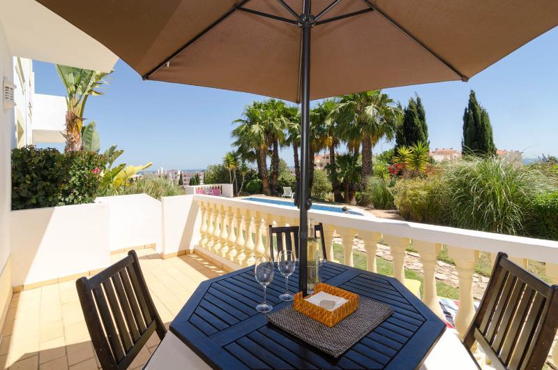 Patio tafel, stoelen en parasol met zicht op tuin