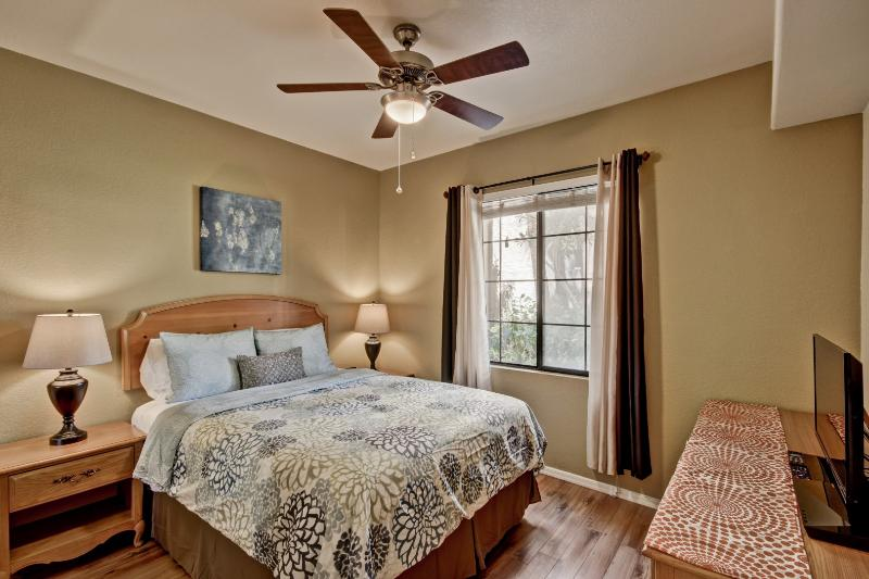 Modern bedroom with a brand new queen bed, flat screen TV, DVD/Bluray player and alarm clock