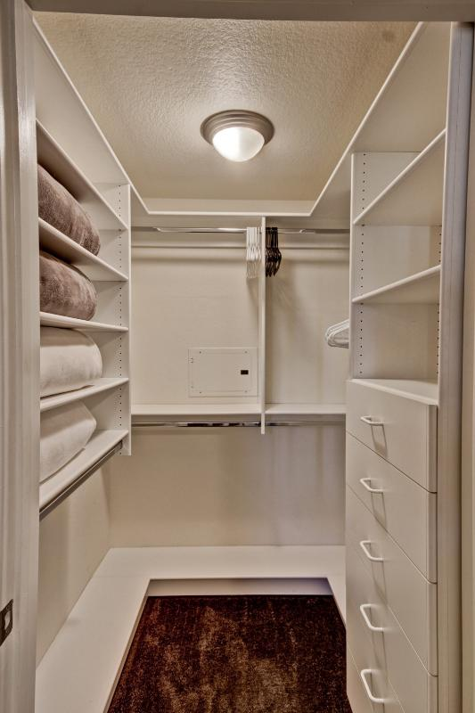 Master bedroom walk in closet with plenty of storage and extra bedding