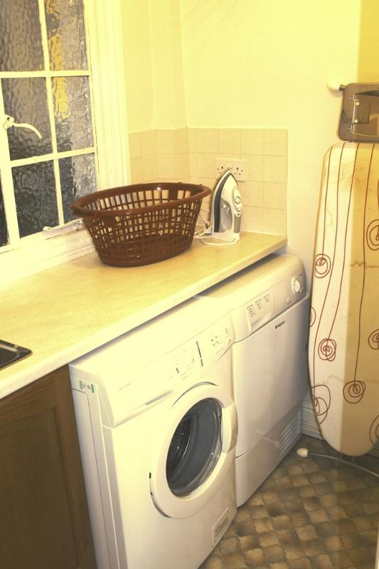Utility room- washing machine, tumble drier, sink, ironing board and iron