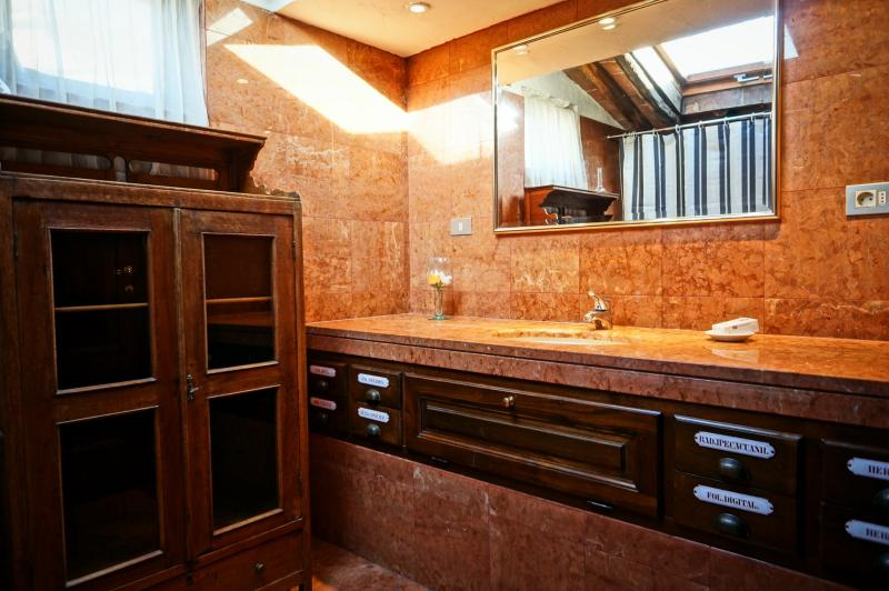 Bathroom features beautiful red marble and antique cabinetry