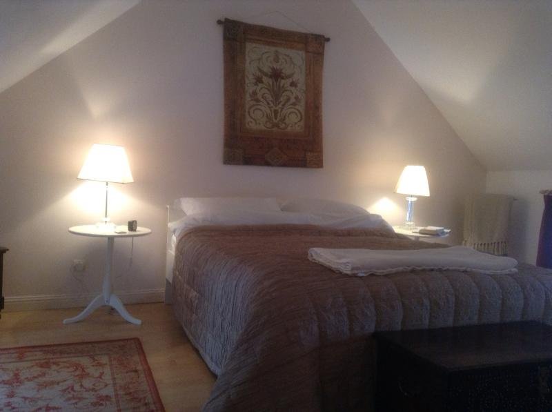 The romantic double bedroom with vaulted ceiling takes up the entire top floor