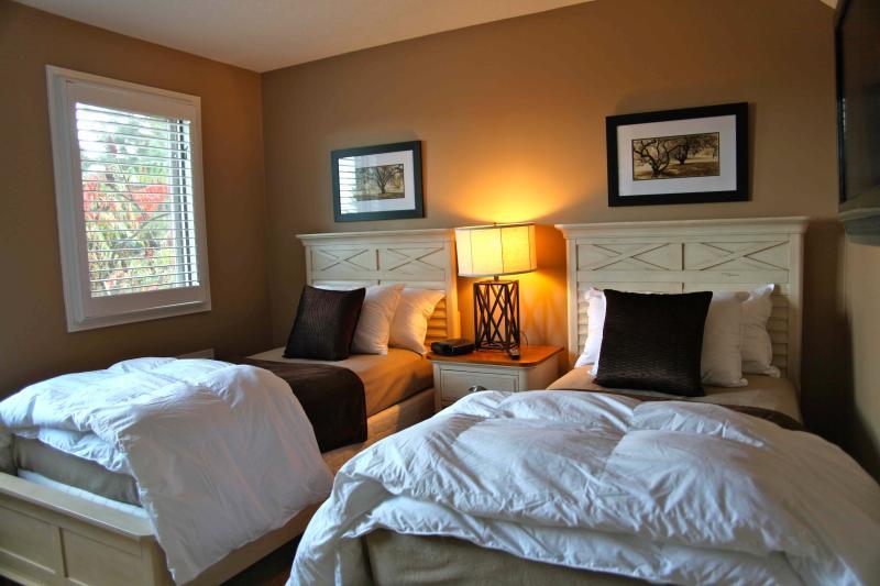 Flexible twin bed configuration in main floor bedroom with flat screen LCD TV.