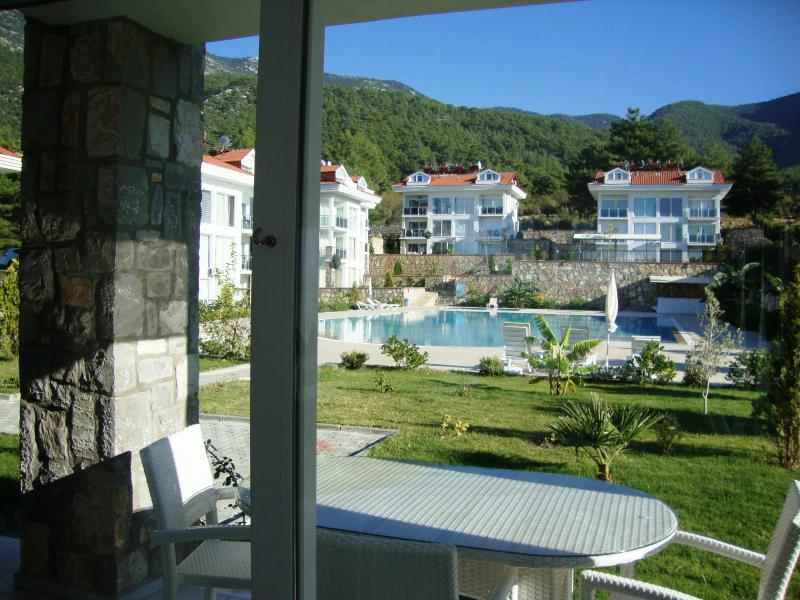 Patio doors from the lounge open onto the terrace with pool and mountain views beyond