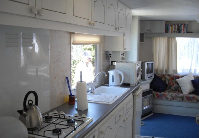 Galley kitchen with oven, hob, microwave and fridge with freezer compartment.