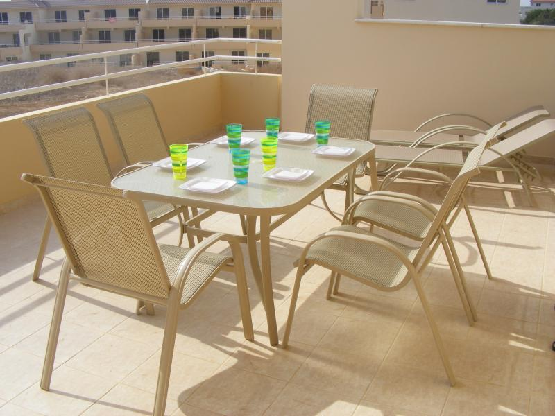 Balcony with patio furniture and sunbeds