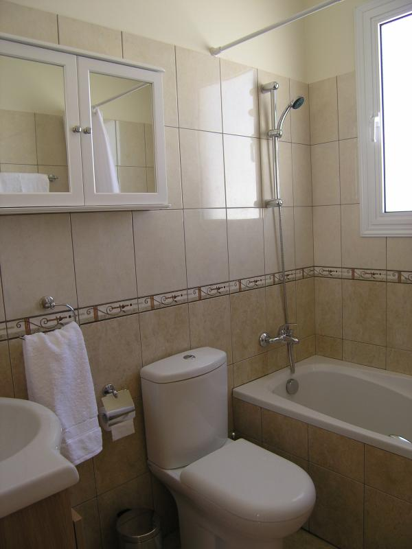 Family bathroom with bath and shower over.