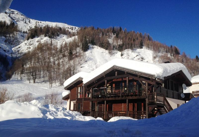 Chalet with snow and sun