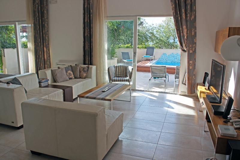 From the spacious living area, large glass doors lead to the terrace and swimming pool