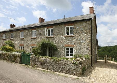 Windover Farm Cottage, with ample gravelled parking area and wooden gates to the rear of the cottage