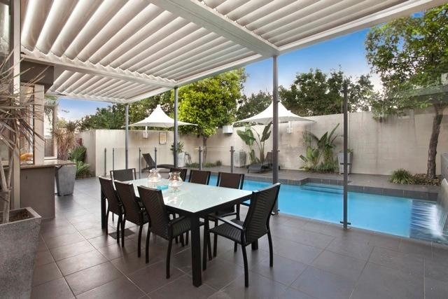 Lower level pool and outdoor dining for 8. All weather vergola blinds overhead with rainsensors.