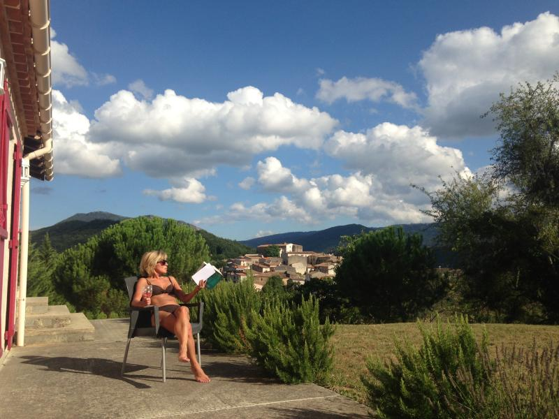 Relaxing with a book,the village of St Ferriol in the background.