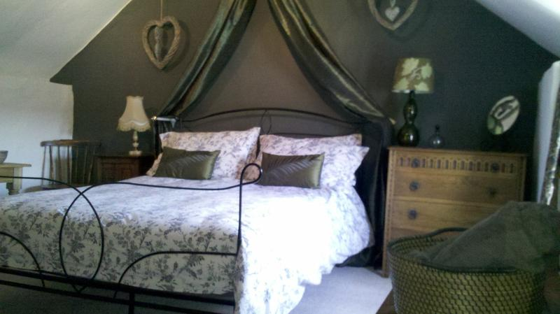 Master attic bedroom with character features and king size bed